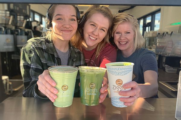 Photo of three smiling baristas holding an iced, blended and hot Matcha Latte