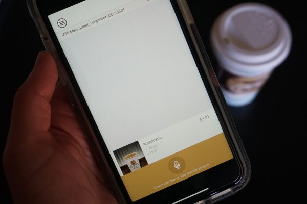 Photo of a hand holding a mobile phone using it to place an order from the Ziggi's Coffee mobile app