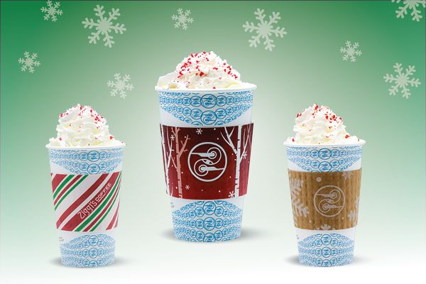 Photo of a peppermint bark drink in a mug topped with whipped cream and candy cane crunch set against a winter scene